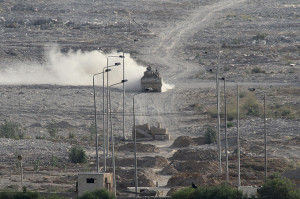 An Egyptian military personnel carrier patrols on the Egyptian side of the border between Egypt and Rafah in the southern Gaza Strip, Wednesday, July 1, 2015. Dozens of Islamic militants unleashed a wave of simultaneous attacks, including suicide car bombings, on Egyptian army checkpoints in the restive northern Sinai Peninsula on Wednesday, killing at least 64 soldiers, officials said. (AP Photo/Mohammed Ebaid)