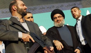 Lebanon's Hezbollah leader Sayyed Hassan Nasrallah (2nd R), escorted by his bodyguards, greets his supporters at an anti-U.S. protest in Beirut's southern suburbs September 17, 2012. Nasrallah made a rare public appearance on Monday to address tens of thousands of marchers protesting against a film made in the United States that mocks the Prophet Mohammad. Nasrallah has been living in hiding to avoid assassination since Hezbollah fought a month-long war with Israel in 2006. REUTERS/Sharif Karim (LEBANON - Tags: POLITICS CIVIL UNREST RELIGION)