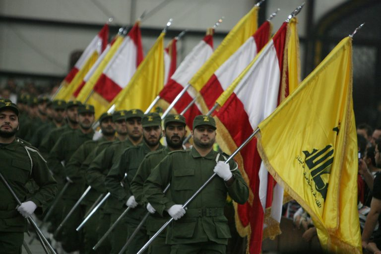 Hezbollah fighters, holding up national flags and the yellow flag of the militant Shiite Muslim group, parade on the occasion of Martyr's Day in the southern suburbs of Beirut November 11, 2009. Lebanon's incoming Prime Minister Saad Hariri announced earlier this week the new cabinet line-up after nearly five months of tough negotiations with his rivals in the Iran- and Syria-backed Hezbollah-led alliance.  AFP PHOTO/RAMZI HAIDAR