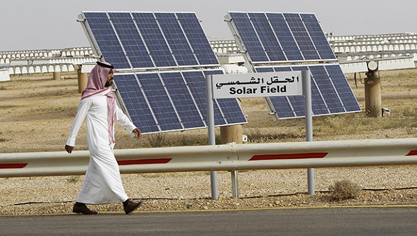 A Saudi man walks on a street past a field of solar panels at the King Abdulaziz city of Sciences and Technology, Al-Oyeynah Research Station in this May 21, 2012 file photo. Saudi Arabia's ambitious plans to become a world leader in installed solar power appear to have run into the sand amid disagreements over their scale, ownership and technology. The world's largest crude exporter announced three years ago it wanted to install 41 gigawatts of solar electricity by 2032 to help meet surging local demand for energy as the Saudi population increases rapidly and the economy grows strongly. REUTERS/Fahad Shadeed/Files