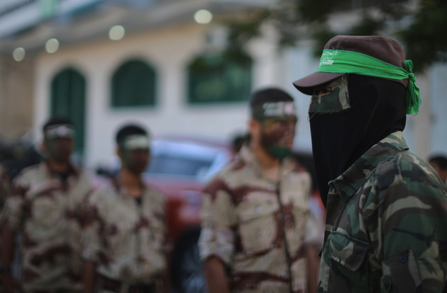KHAN YUNIS, GAZA - JUNE 15:  Young cadets from the Izzedine al-Qassam Brigades, a military wing of Hamas, provide a guard of honour for school students taking part in a graduation ceremony in the town square of Khan Yunis on June 15, 2015, Khan Yunis, Gaza. The devastation across Gaza can still be seen nearly one year on from the 2014 conflict between Israel and Palestinian militants. Money pledged by the international community six months ago to rebuild Gaza has not materialised leaving many Palestinians impoverished and still suffering with the poor economy. United Nations official figures said that the 50 day war left at least 2,189 Palestinians dead, including more than 1,486 civilians, and 11,000 injured. 67 Israeli soldiers and six civilians were killed.  (Photo by Christopher Furlong/Getty Images)