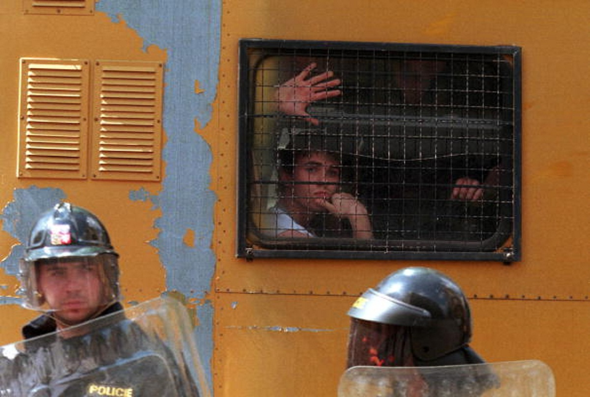 A Demonstrator Looks Out Of The Window Of A Police Paddy Wagon Following His Arrest During A Street Battle Between Police And Anarchists In Central Prague, Czech Republic, May 1, 1999. The Anarchists, Who Were Protesting Against A March By Several Hundred Skinheads, Attacked Police With Rocks And Molotov Cocktails. Several People Were Injured And Approximtaely A Dozen Arrested. (Photo By Sean Gallup/Getty Images)