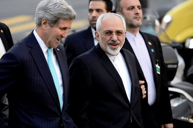 epa04559787 US Secretary of State John Kerry, (L), speaks with Iranian Foreign Minister Mohammad Javad Zarif, (R), as they walk in the city of Geneva, Switzerland, 14 January 2015, during a bilateral meeting ahead of the next round of nuclear discussions, which begin on 15 January.  EPA/LAURENT GILLIERON