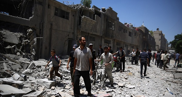 Syrians walk amidst the rubble of buildings in the rebel-held area of Douma, east of the Syrian capital Damascus, following reported air strikes by regime forces, on June 30, 2015. AFP PHOTO / ABD DOUMANY        (Photo credit should read ABD DOUMANY/AFP/Getty Images)